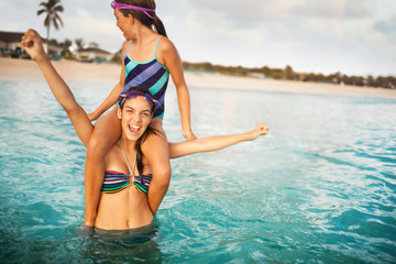 Portrait of a smiling teenage girl carrying her younger sister on her shoulders in the water at the beach.