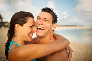 Laughing mid-adult couple hugging on a sandy beach.