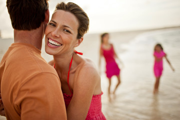 Portrait of a smiling mid-adult woman hugging her husband on a beach.