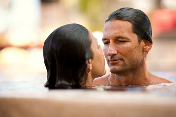 Mid-adult man looking intensely at his girlfriend while standing close to her inside a swimming pool.