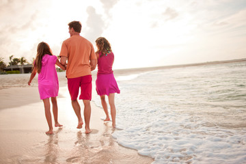 Mid-adult man walking hand in hand with his two daughters along a remote sandy beach.