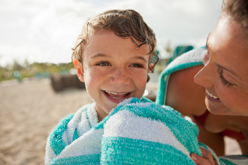 Laughing young boy being wrapped in a towel by his mother at the beach.