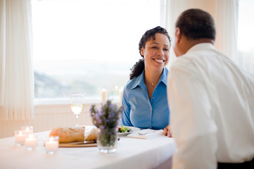 Man and woman smiling at each other over meal