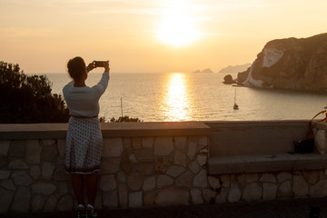 Young woman with smartphone taking pictures of sunset in front of the sea on Ponza island coast, on a wall with view of the ocean.