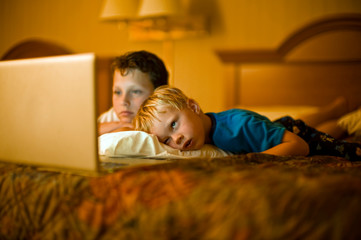 Boy and his younger brother watch a laptop screen with lying front down on a bed together.