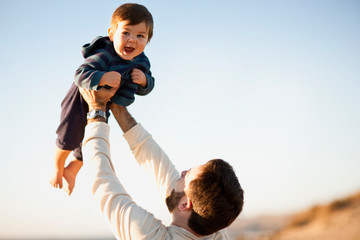 Man holds his son aloft.
