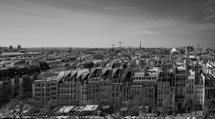 Black and white photo a lot of rooftops and bright sky in Paris