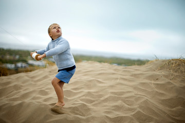 Young boy looks up as he steers a single-string wooden kite reel while standing on a sand dune.