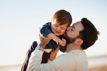 Thirtysomething man kisses his baby son.