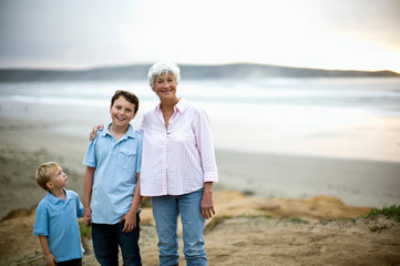 Grandmother and two grandsons pose for a portrait at the beach.