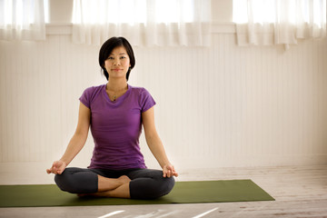 Portrait of a young woman meditating while sitting on a yoga mat inside her home.
