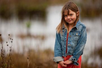 Girl smiles shly as she poses for a portrait outside.