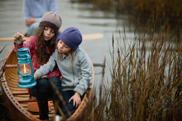 Young girl holds a lit lantern and shows it to her younger sister as they sit together at the prow of a wooden canoe among reeds on a lakeshore.