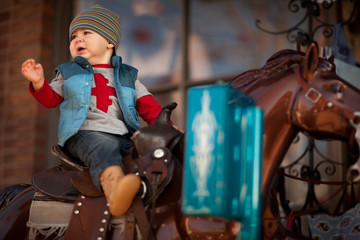 Young boy riding a store-front horse ride.