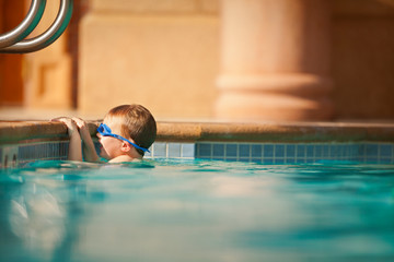 Small boy learning to swim in swimming pool.