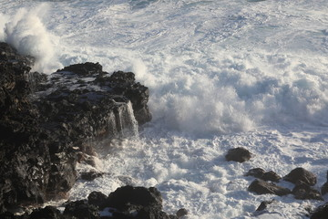 Strong wave of white sea beats on the rocks