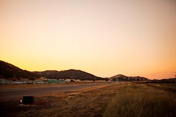Sunset over an airport runway as a plane lands