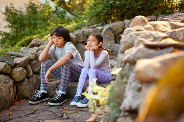 Unhappy brother and sister sitting next to each other on a stone step.
