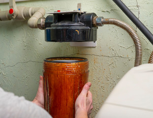 Plumber unscrews glass flask with old water filter in basement.