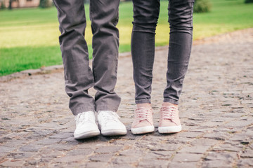 legs of a loving couple in sneakers