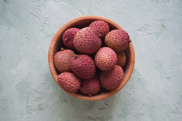 Litchi in a wooden bowl on a grey table.