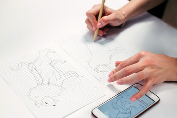 ?lose-up artist drawing craft recycled pencil at paper. Woman painter creating picture of lion looking at her smartphone. Art, talent, craft, hobby concept.