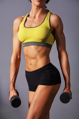 sporty attractive fitness woman with dumbbells in gym