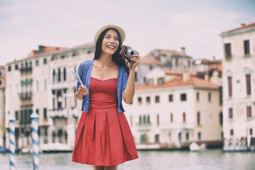 Wall Mural - Travel tourist woman taking photos with vintage camera in Venice city, Italy. Asian girl in red fashion dress on summer vacation happy. Mixed race Asian Caucasian girl having fun traveling outdoors.