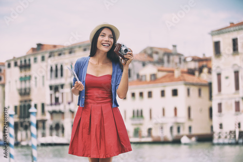 Wall mural Travel tourist woman taking photos with vintage camera in Venice city, Italy. Asian girl in red fashion dress on summer vacation happy. Mixed race Asian Caucasian girl having fun traveling outdoors.