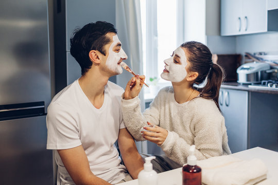 Woman applying clay mask on her boyfriend's face. Young loving couple taking care of skin at home