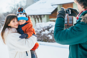 Caucasian father takes pictures on phone of happy mother and little baby toddler son in her arms in snowy winter day outdoor. Family together concept.