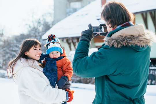 Father takes pictures on phone of happy mother and little baby toddler son in her arms in snowy winter day outdoor.