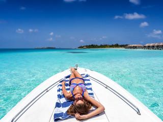 Attraktive, blonde Frau im Bikini liegt auf einem Boot und sonnt sich über den türkisen, tropischen Gewässern der Malediven