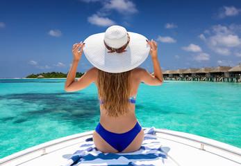 Reisekonzept: Rückansicht einer Frau im Bikini auf einem Boot über türkisem Meer bei einer tropischen Insel der Malediven