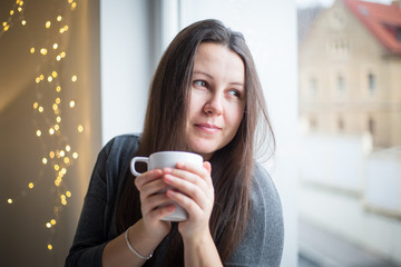Pretty young brunette woman with a cup of tea looking from the window