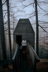 Man in front of a cabin in the woods