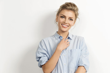 Portrait of stylish caucasian model posing in stylish shirt with tied up hair. Fashionably dressed young woman looking at camera with happiness. Modern fashion concept