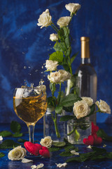 Valentines day. Splash of white wine. Romantic evening. Wine, a bunch of white roses and red hearts on a blue background. Holiday of lovers. A delicious alcoholic drink for two people. Picture photo.