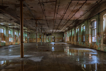 Shabby interior with windows and reflections in  the puddles on the floor inside the abandoned factory building