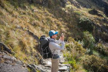 A man takes pictures while on a hike