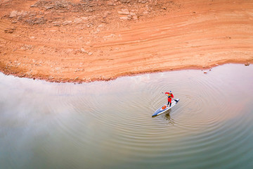 stand up paddler on a  lake