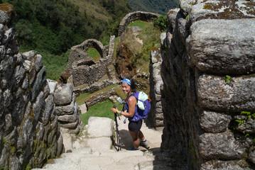 A woman hikes down a steep hill