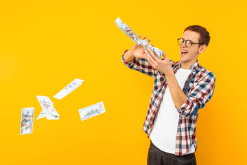 happy man, wearing glasses and a plaid shirt, throwing out money banknotes on a yellow background