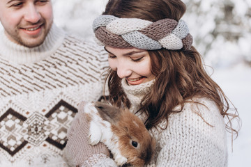 Happy couple playing with cute rabbits outdoors in winter snowy frozen park. Healthy lifestyle, emotional, freedom, happiness concept