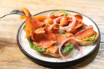 Delicious toasts with smoked salmon, avocado and basil leaves