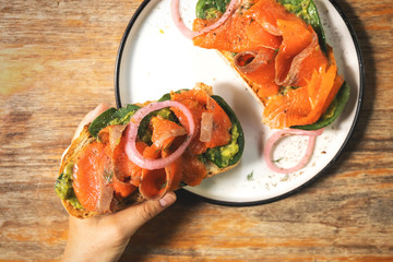 Female hands and delicious toasts with a smoked salmon, avocado and basil leaves