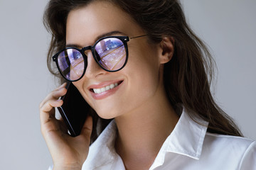 Young businesswoman in eyeglasses talking by smartphone