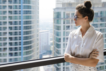 Young businesswoman in her office in the modern building of big city