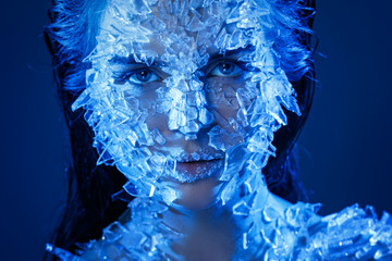 Female face covered with a lot small pieces of glass or ice