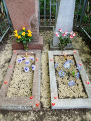 Two halves of one whole. A way to commemorate deceased relatives. Two tombs in one grave. From above them icon lamps are laid out in form heart. The reds-symbolize love, and the whites-restful souls.